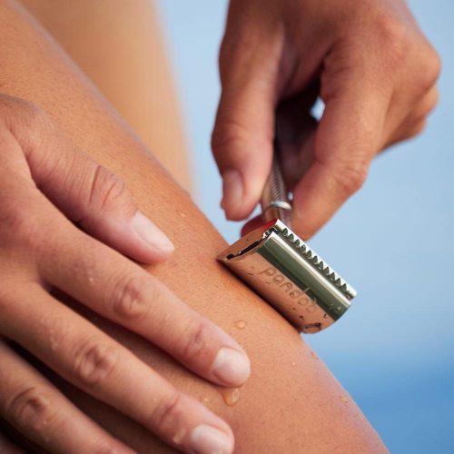 Ein silberner Rasierhobel aus Metall in Benutzung, der Rasierer liegt an einem Bein an