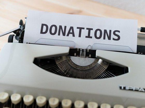 Eine Schreibmaschine mit einem Blatt auf dem Donations steht