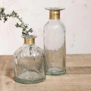 Zwei Vasen aus Glas auf einem Holztisch. Sie haben einen goldenen Messingring an der Öffnung