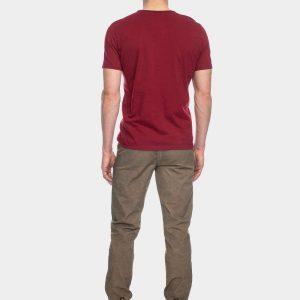 Ein Mann von hinten mit blonden Locken trägt ein rotes Tshirt und eine graubraune Hose.