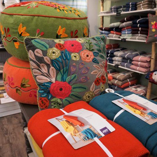 bunte zusammengelegte Picknickdecken und große mit Blumen bestickte Kissen, Bettlaken in einem Regal im Hintergrund