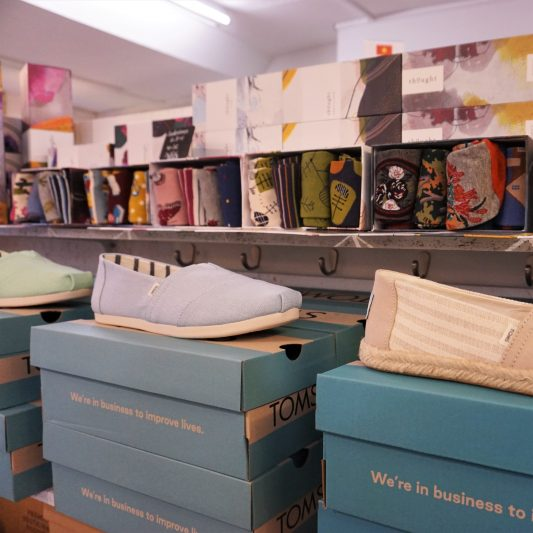Sommerliche hellblaue Schuhe von TOMS mit verschiedenen Motivsocken im Hintergrund im Regal