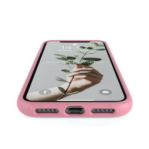 Ein Handy in einer pinken Hülle. Auf dem Sperrbildschirm steht Woodcessoires und man sieht eine Hand die eine Zweig hält.