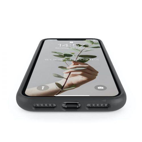 Ein Handy in einer schwarzen Hülle. Auf dem Sperrbildschirm steht Woodcessoires und man sieht eine Hand die eine Zweig hält.