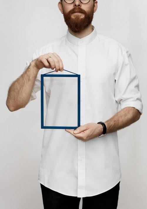 Ein Mann in einem weissen Shirt hält einen kleinen blauen Bilderrahmen in den Händen.