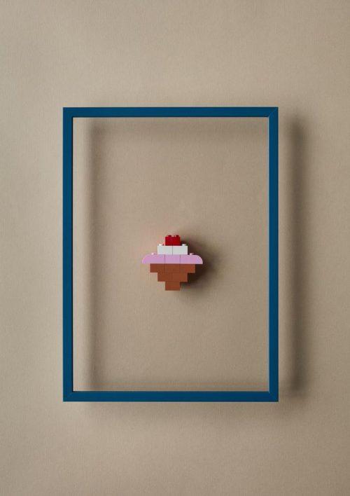 Ein blauer, in der Mitte transparenter Bilderrahmen mit Legosteinen in der Mitte.