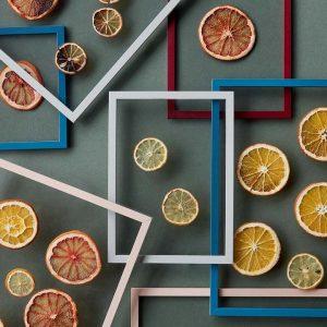 Weisse, rote und blaue Bilderrahmen auf einem grauen Hintergrund. Die Bilderrahmen sind transparent mit getrockenten Orangen und Zitronenscheiben in der Mitte.