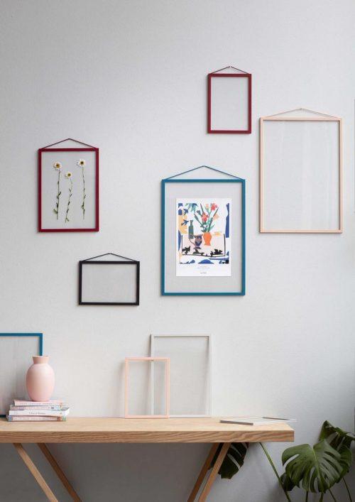 Mehrere bunte Bilderrahmen in verschiedenen Größen hängen an einer weissen Wand. Sie sind alle transparent.
