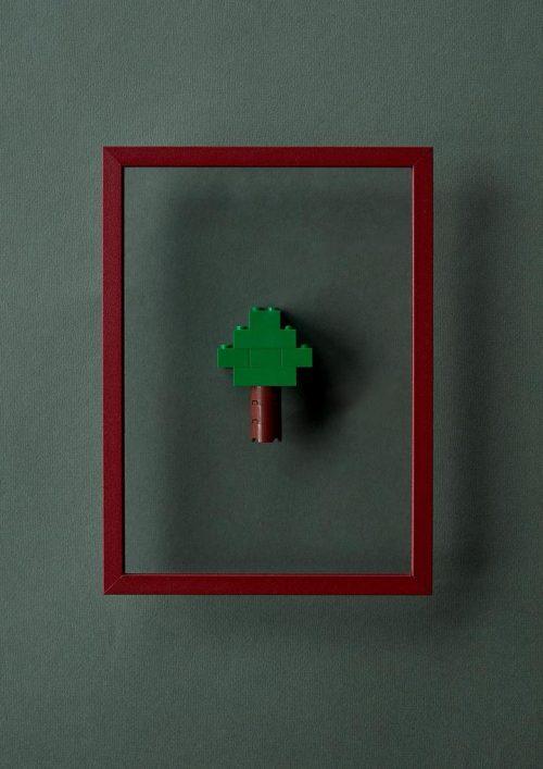 Ein roter dünner Bilderrahmen auf grauem Hintergrund mit einem kleinen Baum aus Legobausteinen in der Mitte.