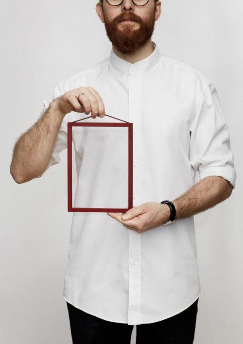 Ein Mann in einem weissen Hemd hält einen kleinen roten Bilderrahmen in der Hand.