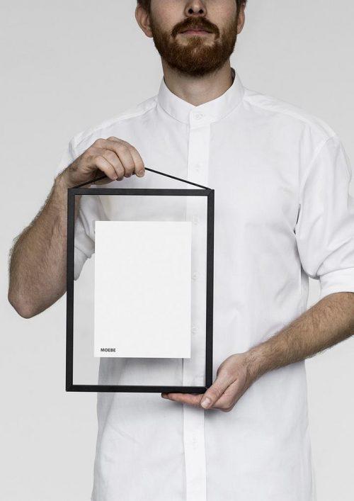 Ein Mann in einem weissen Hemd hält einen schwarzen Bilderrahmen in der Hand.