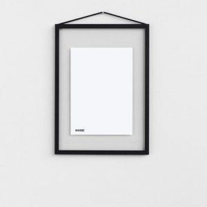Ein Bilderrahmen mit einem durchsichtigen Hintergrund und einem dünnen schwarzen Rahmen hängt an einem dünnen schwarzen Band an einer weissen Wand.