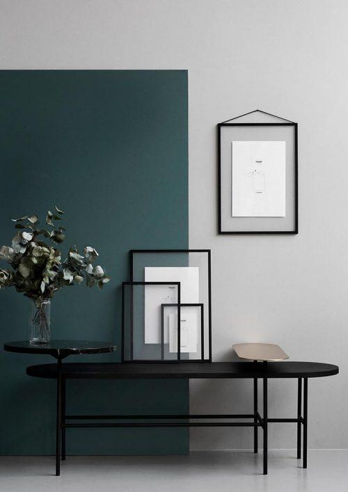 Mehrere unterschiedlichgroße schwarze Bilderrahmen stehen auf einem schwarzen Tisch. Ein großer schwarzer Bilderrahmen hängt an der blauen und türkisfarbenen Wand.